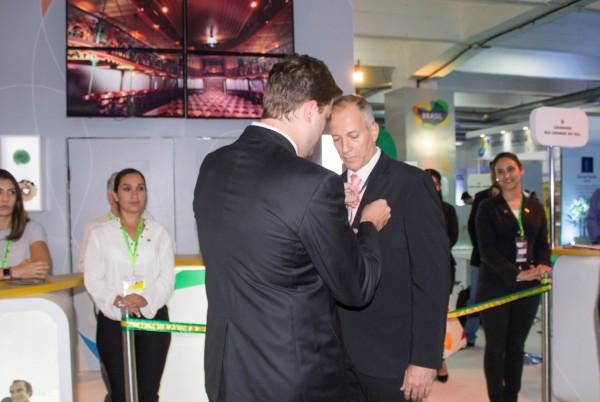 Jose Carlos Brunetti coloca pin de miembro del Comite Descubra Brasil a Romulo Campos de Amaszonas Paraguay